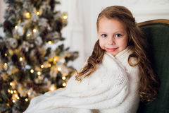 Cute little girl sits by the christmas tree, wrapped in a warm blanket at home Stock Photography