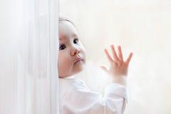Cute little girl sits at window portrait. Cheerful little girl sits at window portrait Stock Photos