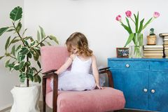 Cute little girl sitting in the armchair at white room with flowers. Fashionable little girl sitting in the armchair at white room with flowers. Horizontal Royalty Free Stock Image