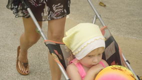 Cute little girl sitting in baby carriage stock video footage
