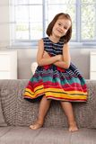 Cute little girl sitting on backrest of sofa Royalty Free Stock Photography
