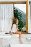Cute little girl sitting on a bathroom window Royalty Free Stock Photo
