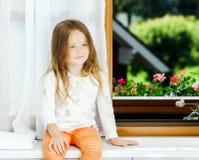 Cute little girl sitting on a bathroom window Royalty Free Stock Photos