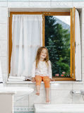 Cute little girl sitting on a bathroom window royalty free stock image