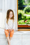Cute little girl sitting on a bathroom window Stock Photos