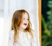 Cute little girl sitting on a bathroom window Stock Photos