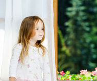 Cute little girl sitting on a bathroom window Royalty Free Stock Images