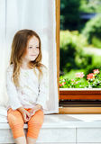 Cute little girl sitting on a bathroom window Stock Image
