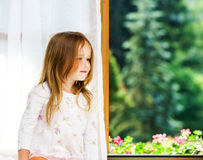 Cute little girl sitting on a bathroom window Stock Images