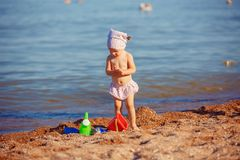 Little girl playing in sand. Cute little girl sitting on the beach and playing with plastic toys royalty free stock photos