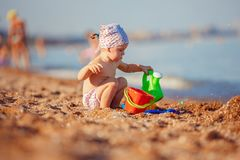 Little girl playing in sand. Cute little girl sitting on the beach and playing with plastic toys stock photography
