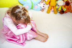 Cute little girl sitting on bed very unhappy stock images