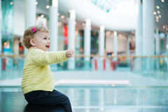 Cute little girl sitting on bench in mall Royalty Free Stock Photography