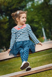 Cute little girl sitting on the bench in a park Royalty Free Stock Images