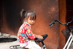 Cute little girl sitting on bicycle at street. Siem Reap, Cambodia Stock Images
