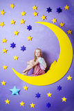 Cute little girl sitting on a big moon Royalty Free Stock Photo
