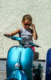 Cute little girl sitting on blue scooter. Street view Royalty Free Stock Photos