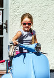 Cute little girl sitting on blue scooter. Street view Royalty Free Stock Image