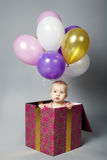 Cute little girl sitting on box with balloons Royalty Free Stock Photography