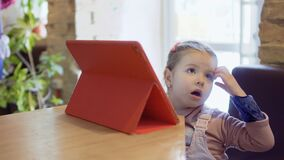 Cute little girl uses digital tablet in the cafe. Cute little girl is sitting in a cafe and uses digital tablet. The girl is watching the cartoons and waits when stock footage