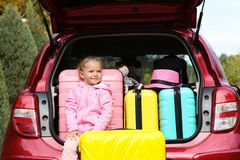 Cute little girl sitting in car trunk loaded with suitcases stock photo