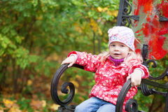 Cute little girl sitting on a chair Stock Images