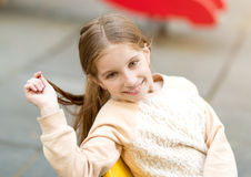 Cute little girl sitting on chair with hair in her hand Stock Photo