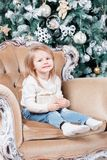 Cute little girl sitting in a chair and opens a box with a present for background Christmas tree with ornaments. Xmas holiday concept. look at the camera Stock Image