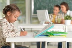 Cute little girl sitting in classroom with teacher and schoolboy royalty free stock photo