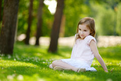 Cute little girl sitting on a clover field Royalty Free Stock Image