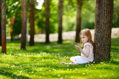 Cute little girl sitting on a clover field Royalty Free Stock Photo