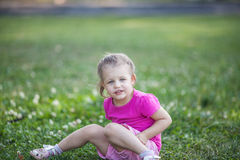 Cute little girl sitting on a clover field. On a sunny summer day Stock Images