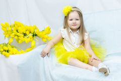 A little girl with a bouquet of yellow tulips. stock photo