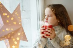 Cute little girl sitting with a cup of hot cocoa by the window a royalty free stock photography