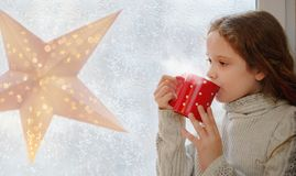 Cute little girl sitting with a cup of hot cocoa by the window stock photos