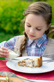 Cute little girl sitting by dinner table and eating Royalty Free Stock Photo