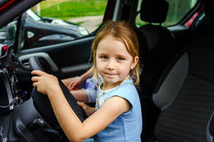 Cute little girl sitting on driver place in a car. Childhood Royalty Free Stock Image