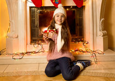 Cute little girl sitting at fireplace with Christmas gift Royalty Free Stock Photos