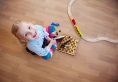 Cute little girl sitting on floor and playing Stock Photo
