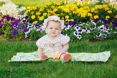 Cute little girl sitting on a flowers meadow Stock Photo