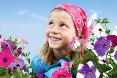 Cute little girl sitting in the garden among the flowers royalty free stock photos