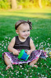 Cute little girl sitting on the grass Royalty Free Stock Photo