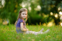 Cute little girl sitting on the grass Royalty Free Stock Photos