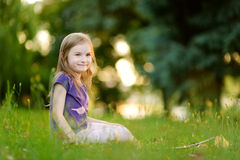 Cute little girl sitting on the grass Royalty Free Stock Images