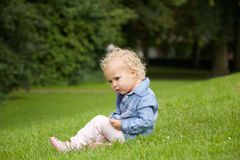 Cute little girl sitting on green grass outdoors Royalty Free Stock Images