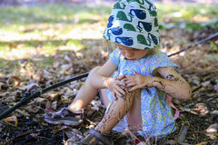 Cute little girl is sitting on the ground , playing in mud Stock Images