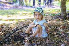 Cute little girl is sitting on the ground , playing in mud Stock Photo