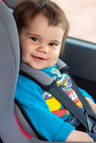 Cute little girl is sitting in her car safety seat Royalty Free Stock Image