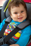Cute little girl is sitting in her car safety seat Stock Photos