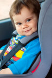 Cute little girl is sitting in her car safety seat Stock Photography